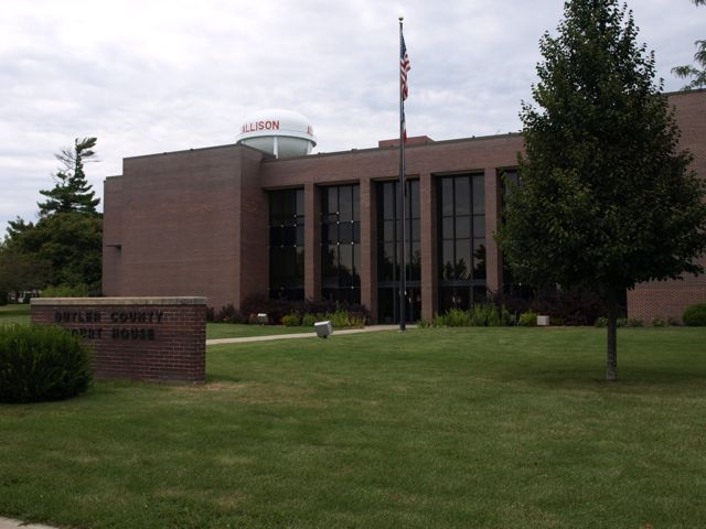 A from the northeast. The dark glass and dark brown bricks provide a tall vertical focal point around the entrance. The flagpole and trees are reflected in the dark glass. The city's water tower is in the background.