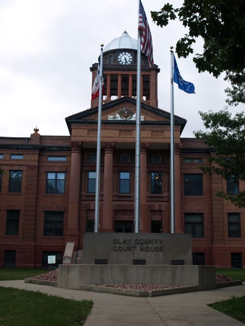 Main entrance of courthouse. Shows tall pillars, and clock tower. Flag poles are in the foreground