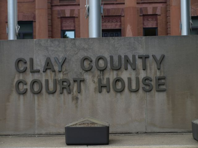 Cement rectangular sign in front of the courthouse. Raised text: Clay County Court House