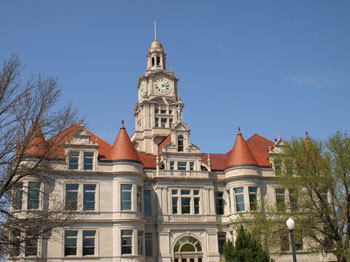 South side of the courthouse. Shows round turret corners, clock tower, and statue of Goddess of Justice