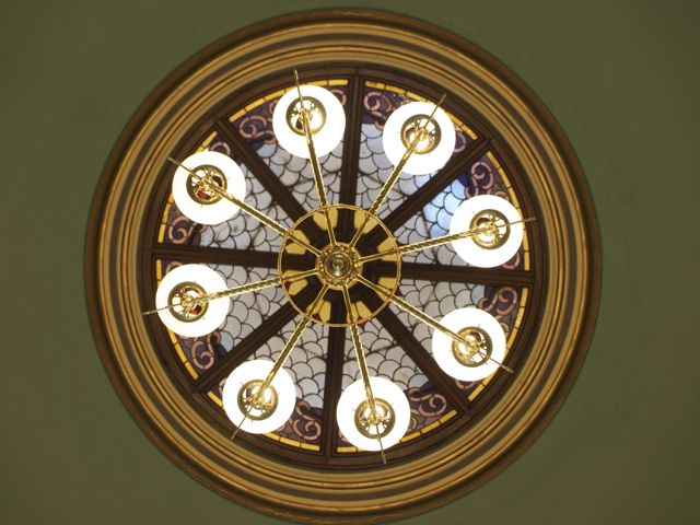 Stained glass ceiling in the rotunda, with light fixture centered in the foreground