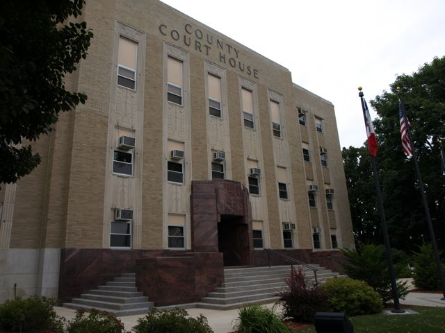 View of courthouse from the northeast. Shows front of courthouse, wide steps leading to door, and beautiful polished stone around the steps and door