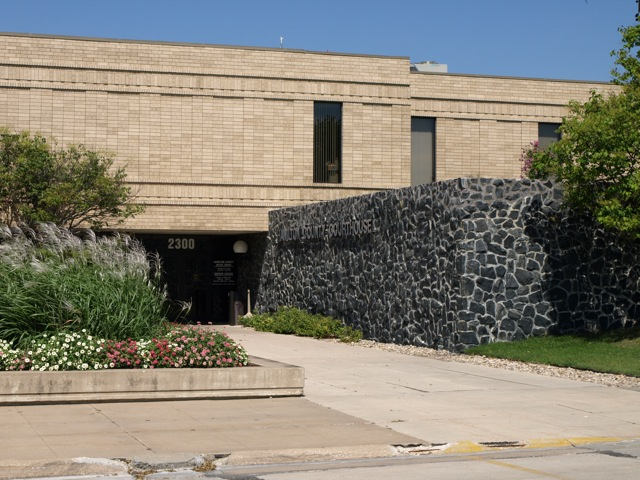 South entrance of building, with flowered landscaping on the west side of the sidewalk, a black and grey stone wall on the east.