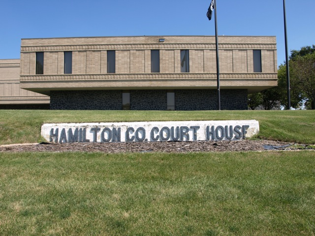 "A closer view of the west side of the courthouse. A cement slab lies in the grassy slope, with large grey letters ""Hamilton Co Court House"""