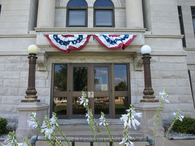 Close view of east entrance. Brass pillars support round light globes. Red white and blue bunting above door