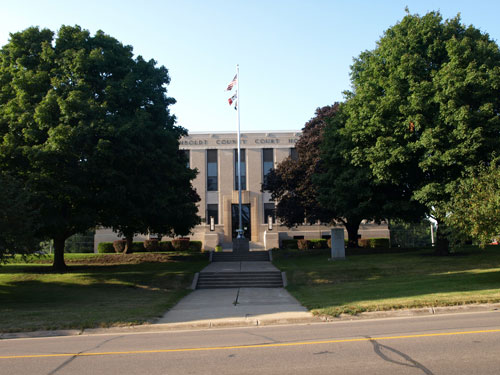 Wide view of the courthouse, partially occluded by trees. A war memorial and flagpole are in the courthouse lawn south of the building