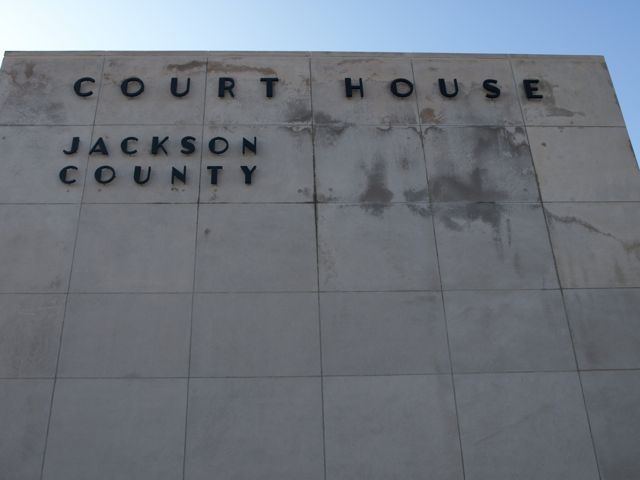 "A closer view of the grey stone blocks. Raised black text ""Court House Jackson County"""