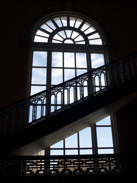 Wrought iron staircase in sillouette against an arched window. Sky and buildings east of the courthouse are in the background.