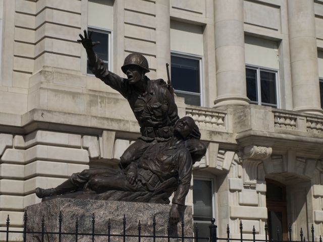 The soldier memorial on the south lawn with courthouse in background. One soldier is holding a wounded comrade, and signals for help.