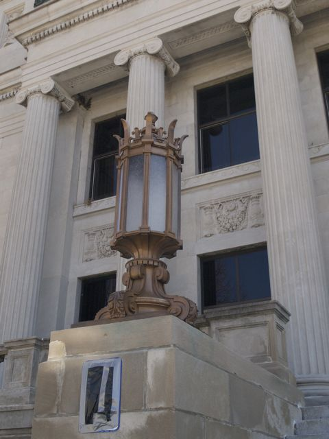 Close view of a light fixture in front of the courthouse. Decorative metal surrounds the white glass.