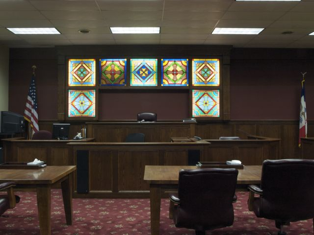 A view of the courtroom, facing the bench. There are seven stained glass window sections on the wall behind the bench.