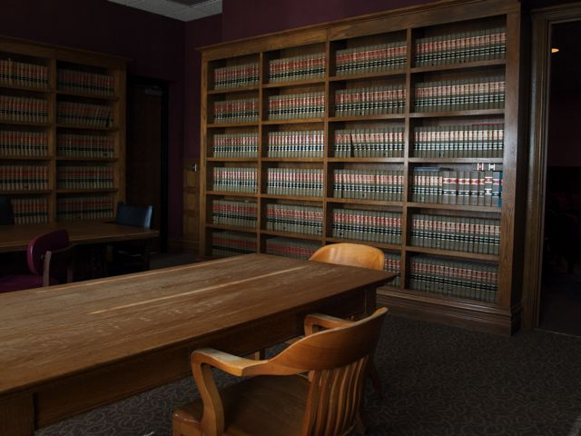 wood chairs and table in the foreground, with shelves of law books in the background