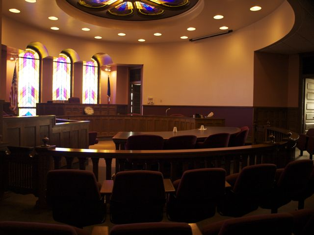round court room, with dark wood and lighted by stained glass and recessed lights