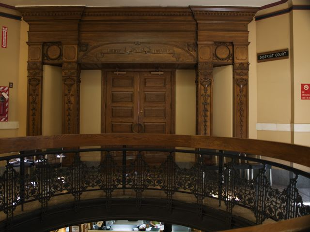 Curved wood railing with wrought iron supports around the rotunda; hand-carved wood detail around the courtroom door.