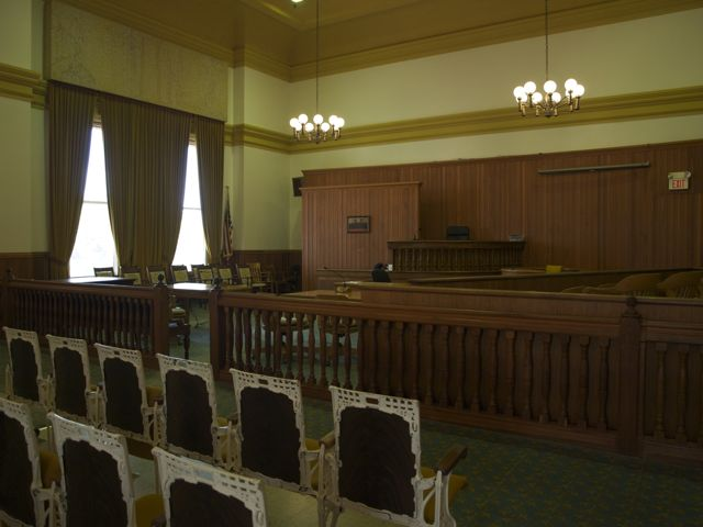 A view of the judge's bench from the southeast corner of the courtroom. Gallery seats are in the foregrounds, and the carved bar is in the center of the photo