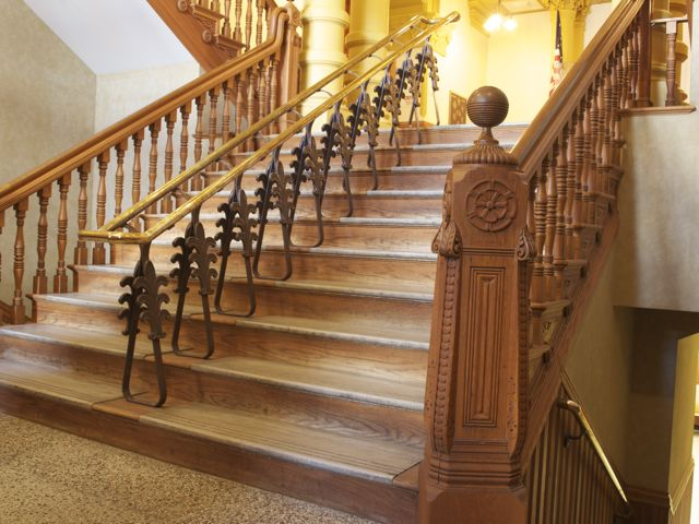 A view of the stairs leading from the entrance to the main floor lobby. Intricate oak carving and iron details on the rail support