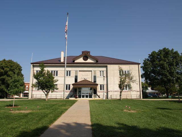 Distant view of the south side of the courthouse, includes flagpole and main entrance
