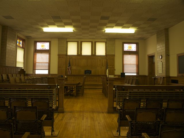 View of courtroom from the rear. The gallery seats are iron and wood; the attorney tables and chairs and judge's bench are carved wood.