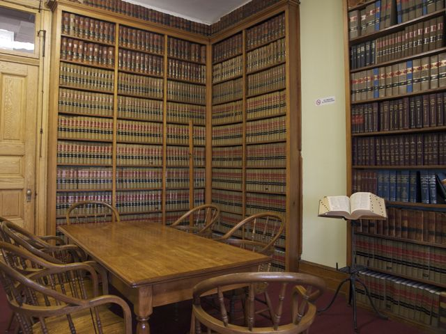 Tables and carved chairs in front of shelves filled with law books. A bookstand is on the left