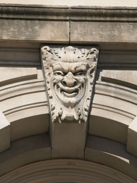 Grotesques are carved into the stone in the arches above the windows