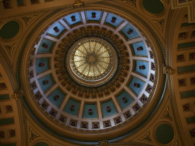 circular stained glass ceiling, with gold and blue designs in the dome surrounding the glass
