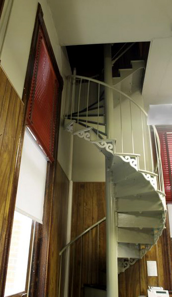 A metal spiral staircase leads from the clerk of court office to the back of the courtroom. It is painted white