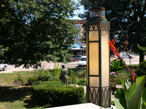 Close view of the light fixture, with metal details and cream glass. A sculpture garden is in the background.