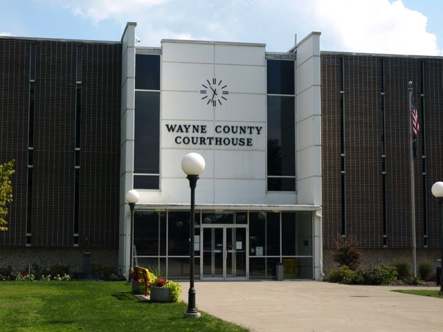 "Front entrance on the west side of the building . Shows text ""Wayne County Courthouse"" below clock face."